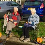 Couple sitting on bench with pumpkins